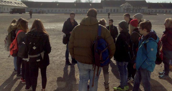 Die Montessori-Klasse 9/10 auf dem Appellplatz bei Ihrer Führung durch die KZ-Gedenkstätte Dachau. Im Hintergrund sieht man das Wirtschaftsgebäude und die mahnenden Kunstwerke der Überlebenden.